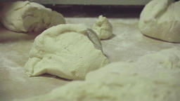Dough at table on bakery HD video. Baker hands take dough. Bread production Image