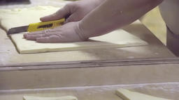 Baker cuts raw flaky dough to portion pieces HD video. Bakery croissant prepare Footage