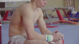 Young gymnast sitting in gymnasium HD video. Athlete emotional look Footage