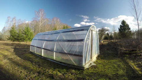 plastic greenhouse in spring farm and evening clouds, time lapse 4K Footage