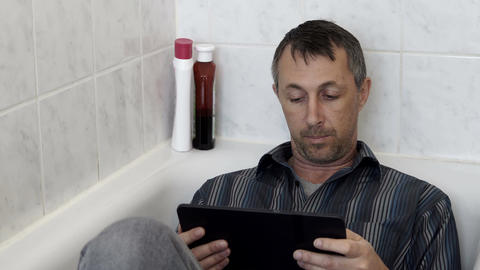 Man In Bathroom Bathtub Clothed With a Tablet Footage