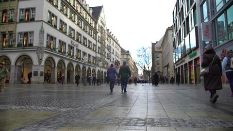 People walking on St. Mary square with lots of stores in Munich, shopping Footage