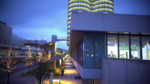 View on tall illuminated business building, modern architecture, decorated trees Footage