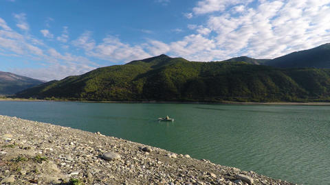 Man in boat sailing down river on a sunny day, serene mountain landscape, travel Footage
