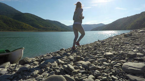 Young woman jogging along pebbled sunlit riverbank in the mountains on sunny day Footage