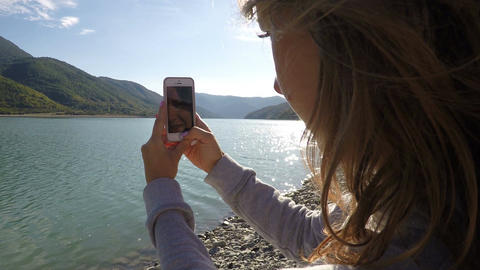 Female filming mountain landscape and river on cell phone on a sunny day Footage