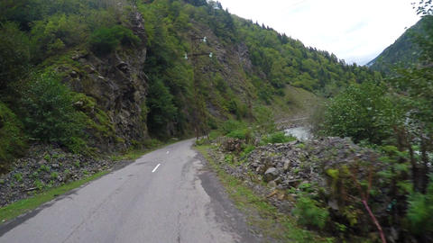 Riding on winding mountain road along fast-streamed river and steep cliffs Footage