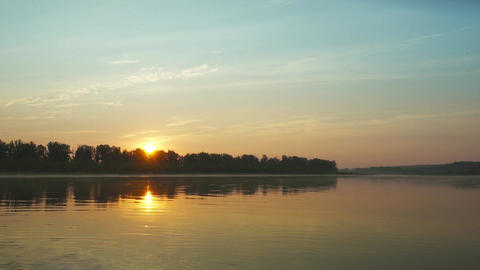 Landscape with sunrise over big river, pan view 4k Footage
