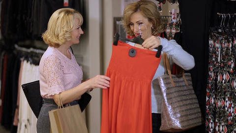Mature women choosing dress in clothing store Footage