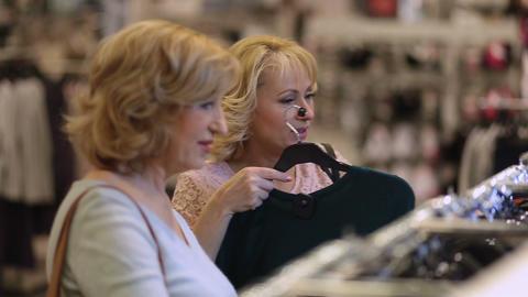 Senior women choosing dress while shopping in shop Live Action