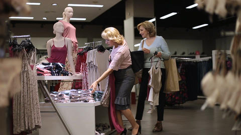 Beautiful women shopping for clothes at store Live Action