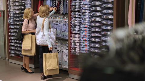 Women choosing necktie during apparel shopping Live Action
