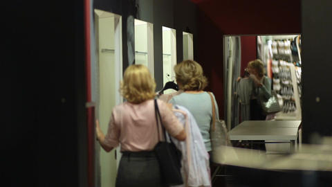 Happy shopaholic women entering fitting room Live Action
