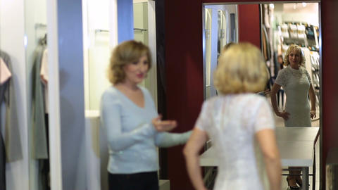 Excited lady choosing dress in store fitting room Live Action
