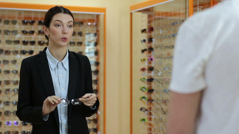 Charming optician selling glasses in optical shop Live Action