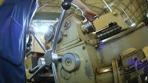 Closeup Worker in Uniform Operates at Huge Lathe in Workshop Footage