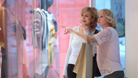 Excited women looking at clothes in store window Footage