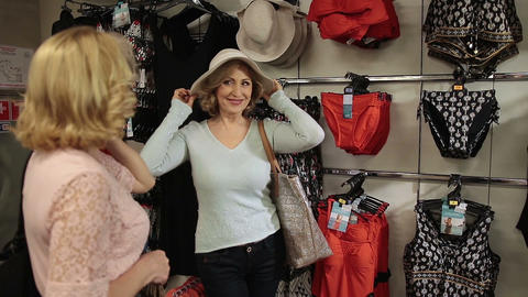 Shopaholic woman trying elegant hat on in store Live Action