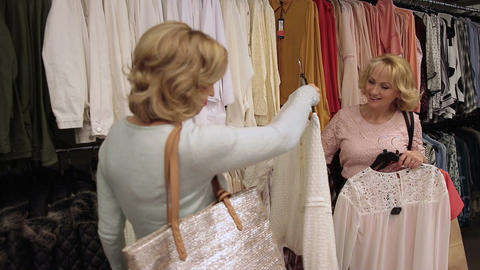 Beautiful shopaholic women buying clothes in store Live Action