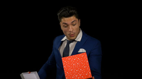 Man gets excited and surprised when opening his birthday gift box Footage