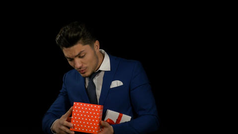 Handsome attractive young man opening gift box and showing it to the camera Footage