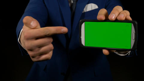 Close up with hand of a man inviting you to look at smartphone with green screen Live Action