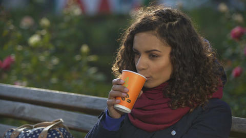 Frozen female drinking coffee to get warm, waiting for friends sitting on bench Footage