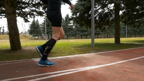 Close-up slow motion shot of a man legs jogging on the course track Footage