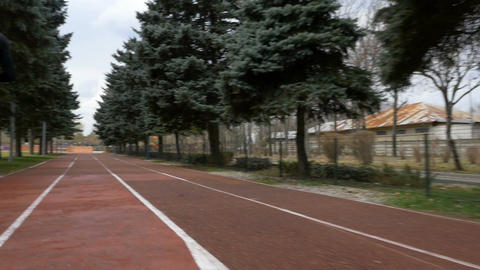 Back view of man jogging in slow motion on a course track Footage