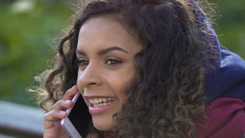 Young attractive female talking with her friend over mobile phone, closeup Footage