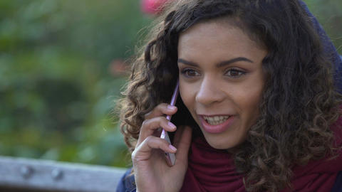 Happy mixed race woman talking over smartphone outdoors, smiling, ending call Footage
