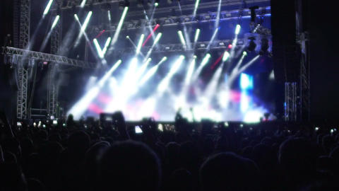 Crowd of people watching fantastic rock star performance on illuminated stage Footage
