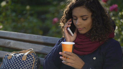 Attractive mixed race woman talking over phone and drinking coffee outdoors Footage