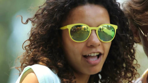 Attractive biracial girl in yellow sunglasses dancing, singing among friends Footage