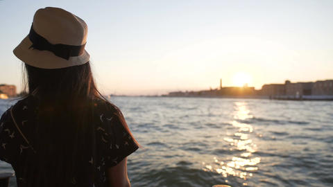 Romantic young lady enjoying Venice sunset alone on board of vaporetto water bus Footage