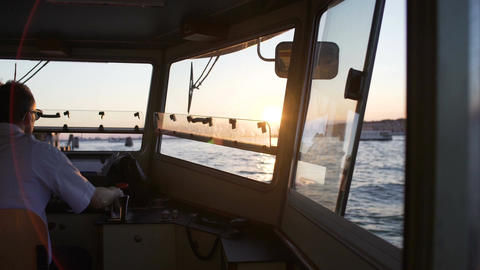 Male captain driving ship with steering wheel, water traffic, transportation Footage