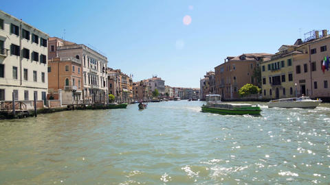Old architecture of Venice streets seen from canal, sunlight sparkling on water Footage