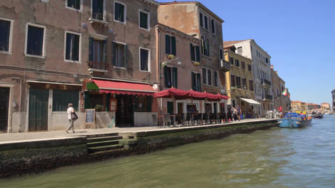 People walking old street with cafe along canal, slow-paced life in Venice Footage