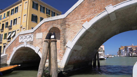 Vaporetto water bus moving below old pedestrian bridge across canal in Venice Footage