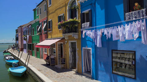 Colorful houses and boats moored along canal on Burano island, locals in street Footage