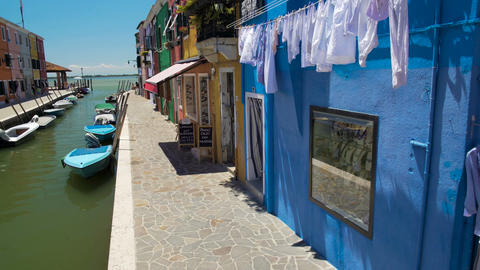 Creative colorful houses on Italian Burano island, motorboats moored at sidewalk Footage