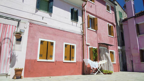 Old colored residential houses on Burano island, hot summer day in Italy, Venice Footage
