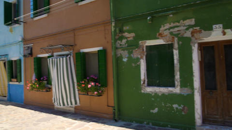 Shabby house neighboring nice multicolored buildings, colorful street on Burano Footage