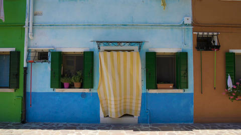 Brightly painted blue house in multicolored street, Burano island architecture Footage