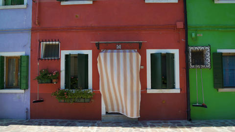 Cozy house painted in red color, famous colorful architecture on Burano island Footage