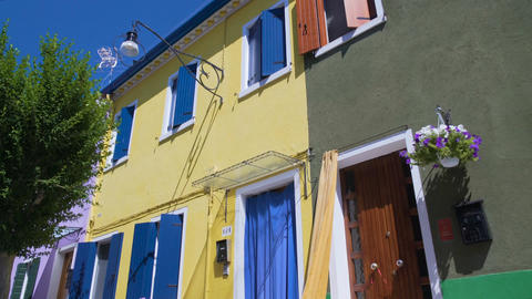 Bright yellow dwelling house neighboring well-kept colorfully painted buildings Footage