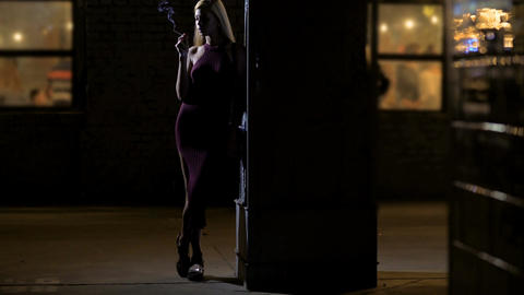 Lonely blond lady enjoying cigarette smoke while standing alone near night club Footage