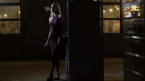 Drunk blonde female dancing and smoking near concert hall, nightlife, bad habits Footage