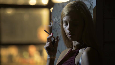 Thoughtful attractive woman smoking cigarette, night life, bad habits, relax Footage