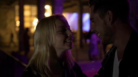 Couple in love standing near night club and talking, first date, relationship Footage